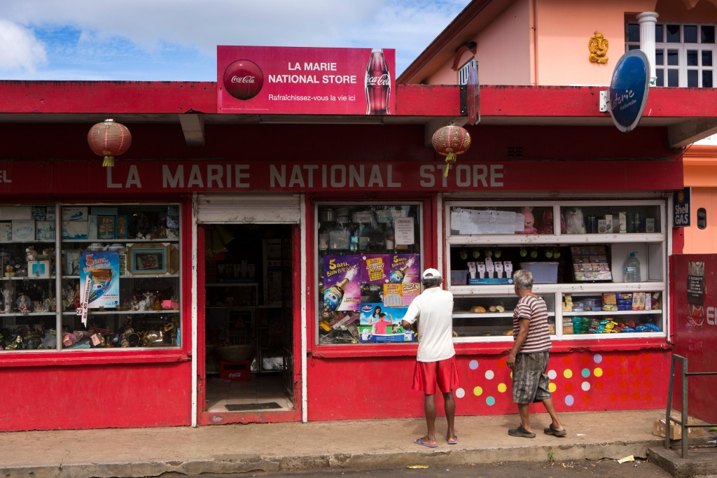 EDJX8X Mauritius, Vacoas, men outside La Marie National Store, red painted rural shop